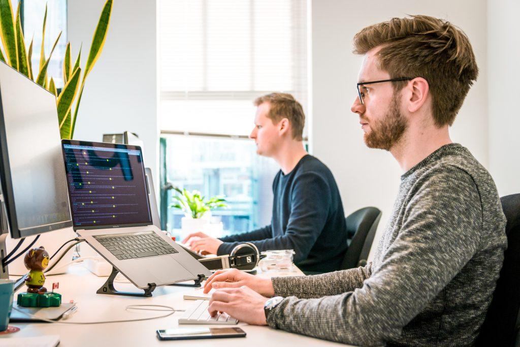 Kaksi miestä työssä tietokoneiden ääressä.