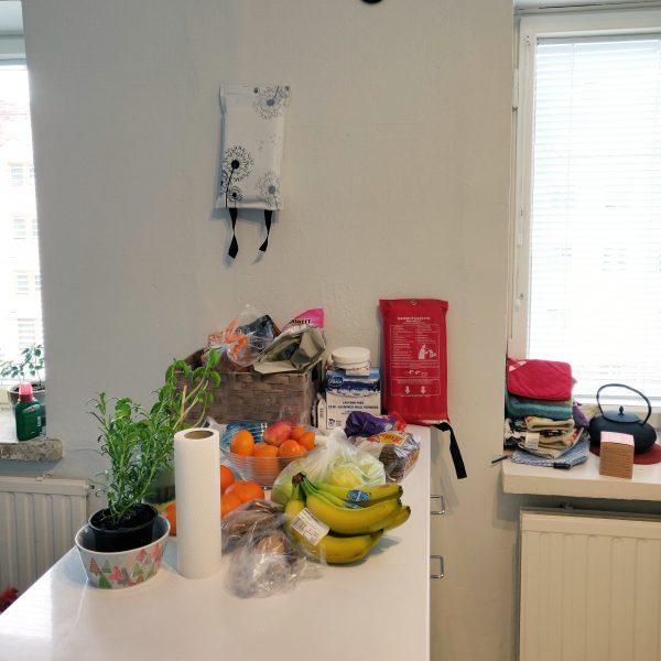 Keittiön pöydällä taloustavaraa ja ruokatarvikkeita.